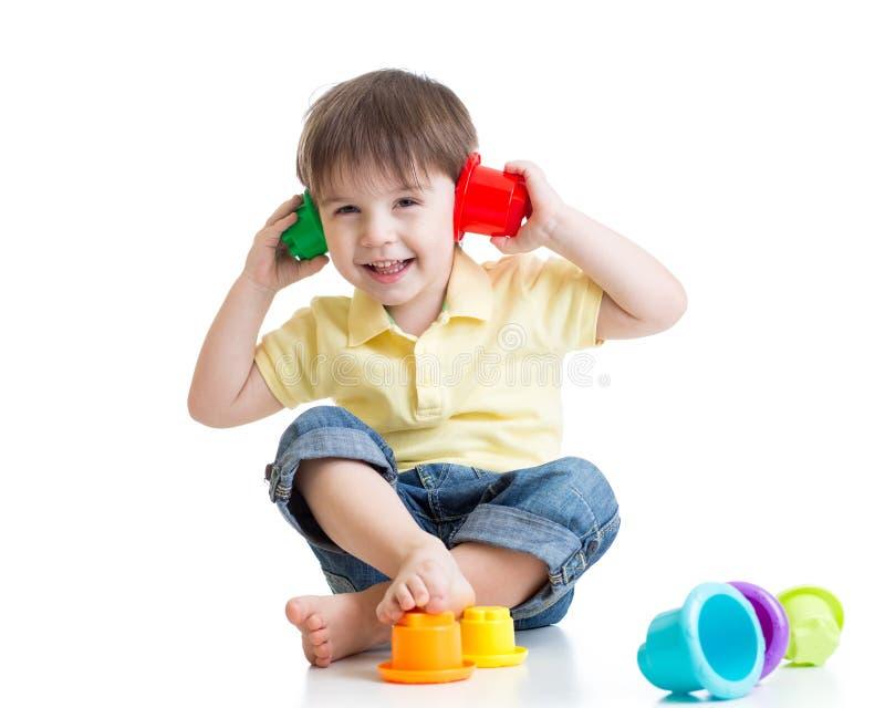 peu d 39 enfant joue avec des jouets tout en se reposant dessus photo stock image du amusement. Black Bedroom Furniture Sets. Home Design Ideas