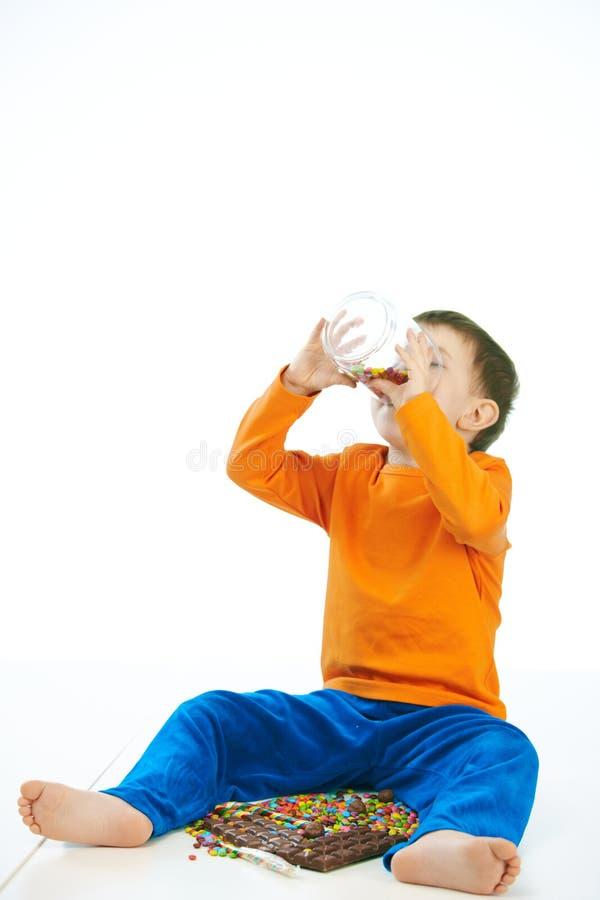 Peu d'enfant mangeant des bonbons du pot en verre à la maison photos libres de droits