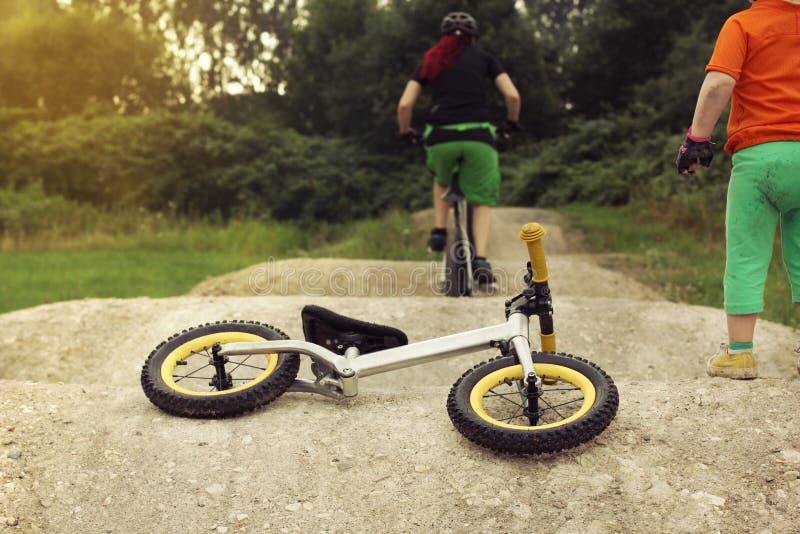 Peu d'enfant observant sa maman d'une chevelure rouge monter un vélo sur un pumptrack avec l'excitation, vélo d'équilibre se trou photo libre de droits