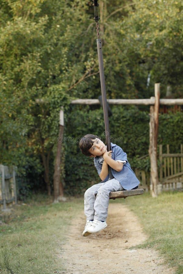 Peu d'enfant s'asseyant sur le funiculaire de jouet dans un terrain de jeu d'enfants photographie stock