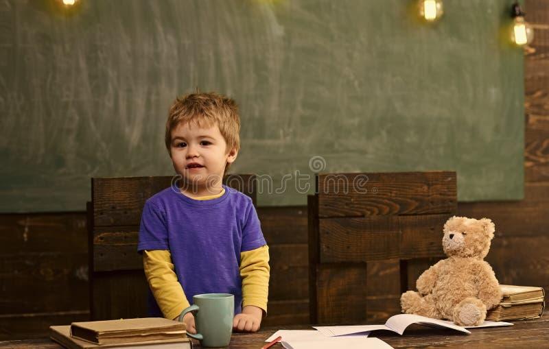 Peu d'enfant se tenant derrière le bureau en bois Table en bois foncée avec les cahiers, l'ours de nounours, la tasse et la pile  photographie stock libre de droits