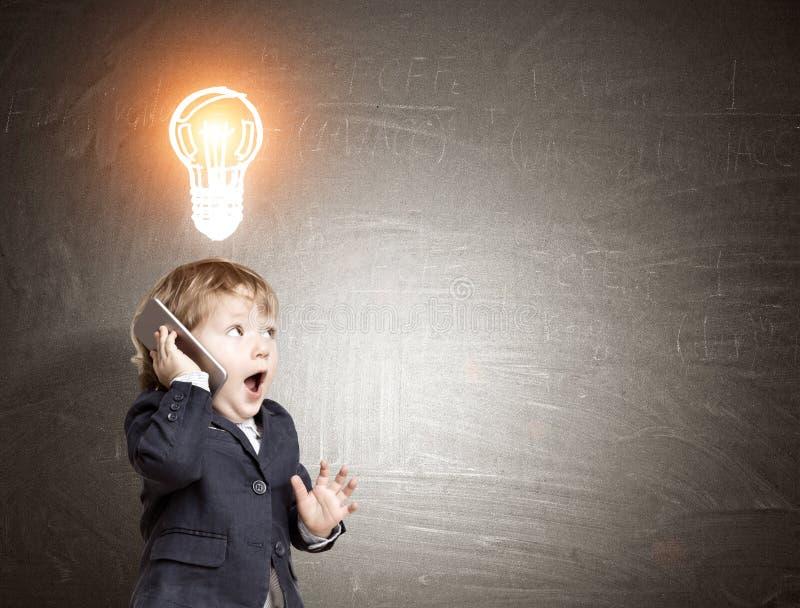 Peu d'enfant sur le téléphone et un croquis d'ampoule sur le tableau noir image stock