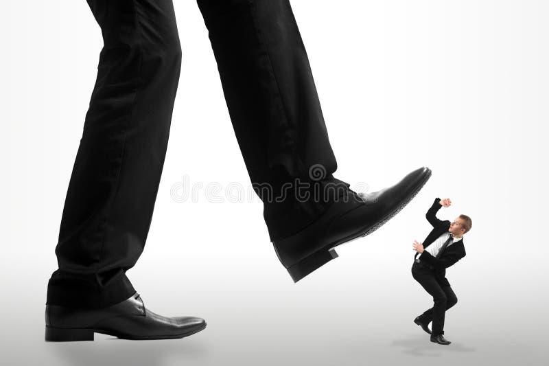 Peu d'homme d'affaires écrasé par les pieds d'a photographie stock