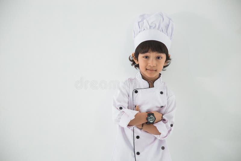 Peu d'uniforme de profession d'enfant feignant pour être un chef photos stock