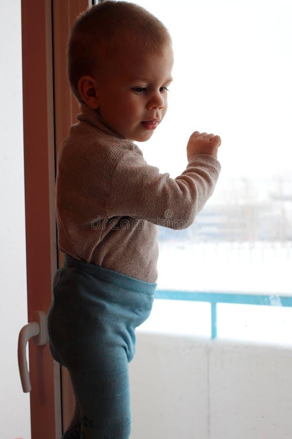 Peu de bébé garçon s'est élevé sur un haut rebord de fenêtre regardant le danger de sourire de fenêtre photos stock