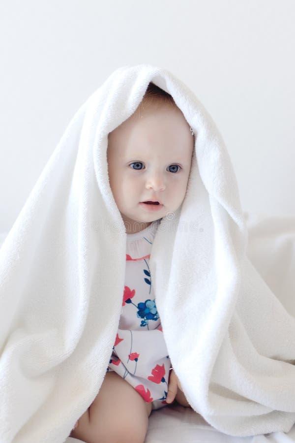 Peu de bébé sourit d'un air affecté sous le tapis de biege photographie stock libre de droits