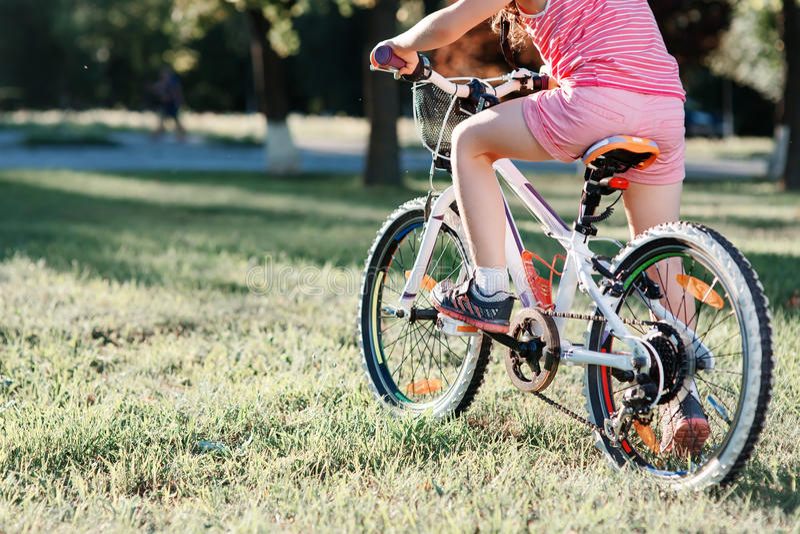 Peu de bicyclette d'équitation de fille de brune en parc au coucher du soleil photographie stock