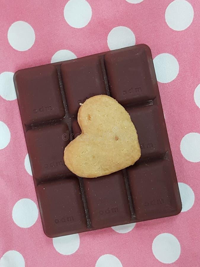 peu de biscuit de beurre de coeur sur le chocolat pour des valentines avec les points de polka roses photos stock