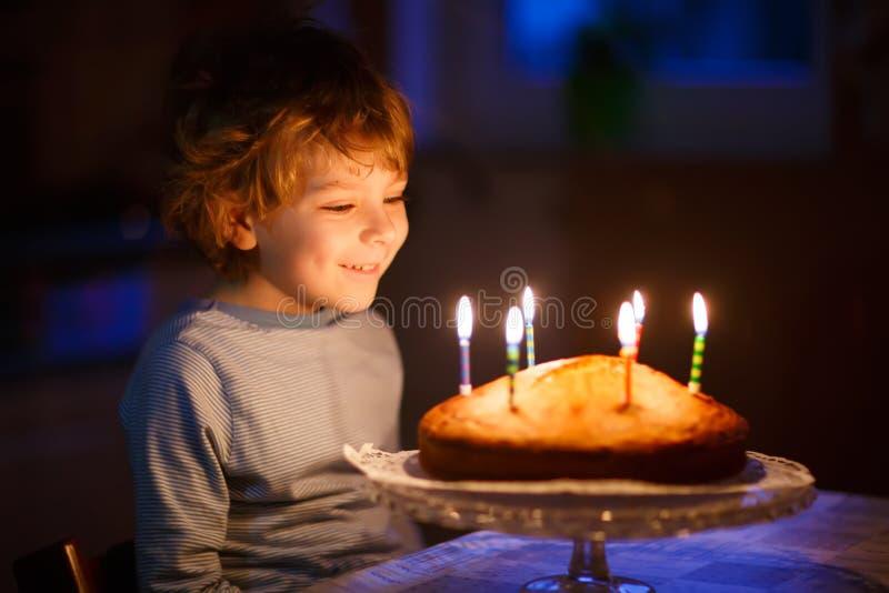 Peu de bougies de soufflement de garçon d'enfant sur le gâteau d'anniversaire images libres de droits