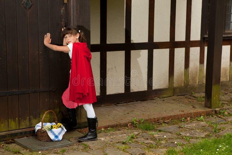 Peu de capot d'équitation rouge à la maison de la grand-maman photographie stock libre de droits
