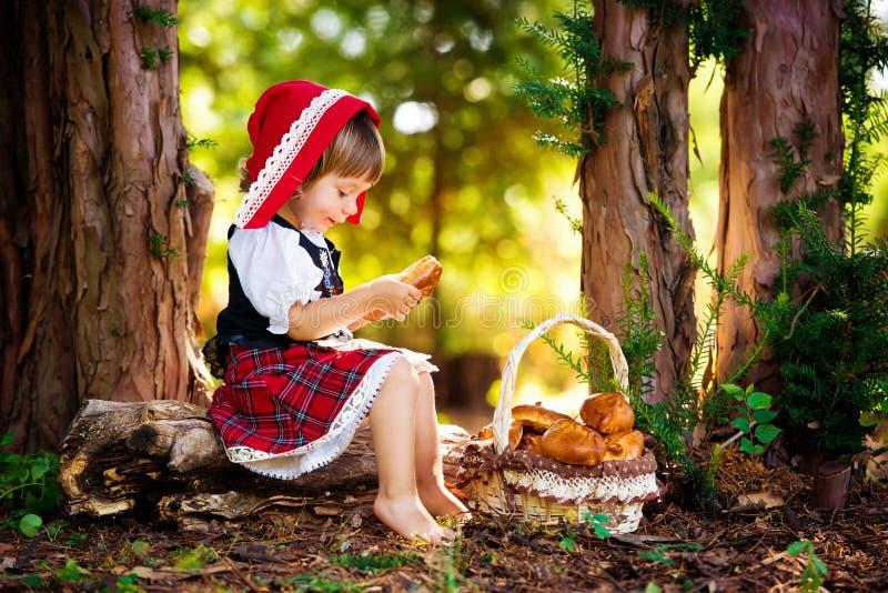Peu de capuchon rouge dans la forêt se repose sur un rondin avec un panier des tartes image stock