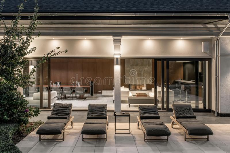 Peu de chaises de plate-forme sur la terrasse carrelée de la villa lumineuse image stock