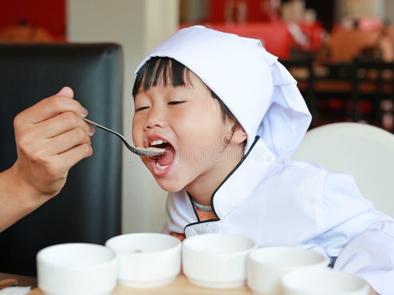 Peu de chef doit apprendre manger de la nourriture savoureuse photo stock