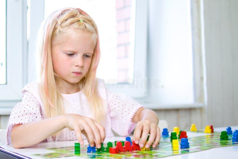 peu de fille blonde joue - des chiffres de personnes de prise à disposition déchets de bois jaunes, bleus, verts chez le jeu des  image stock