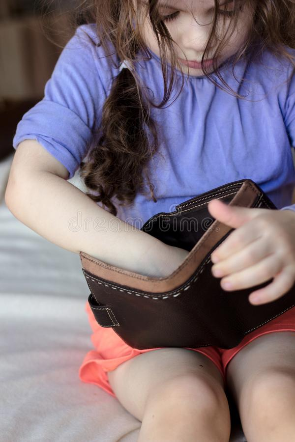 Peu de fille d'enfant avec le portefeuille vide dans des mains photos stock