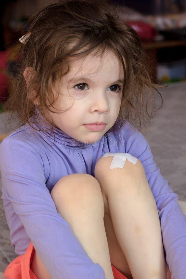 Peu de fille d'enfant avec le sparadrap sur le genou images stock
