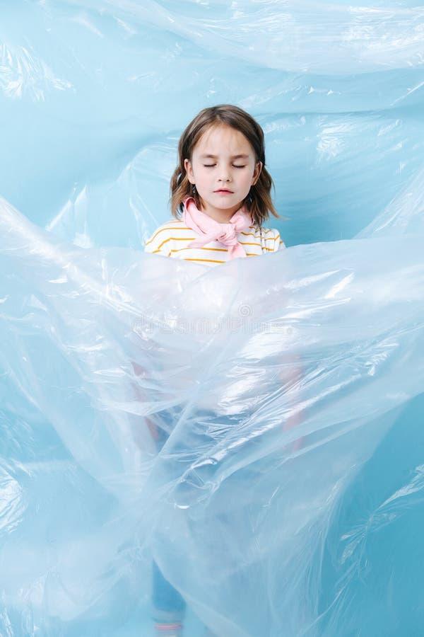 Peu de fille est enveloppée en plastique dans la protestation de la crise de rebut photographie stock