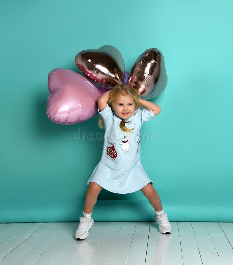 Peu de fille a l'amusement avec un groupe de ballons ? air roses sous forme de son coeur images stock