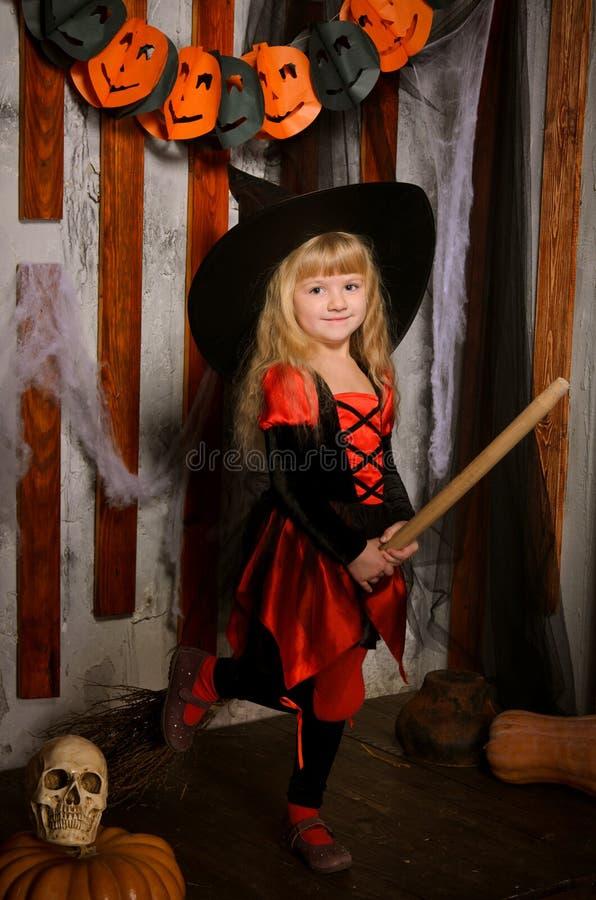 Peu de fille mignonne de sorcière de Halloween sur le balai photographie stock