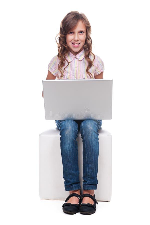 Peu de fille souriante avec l'ordinateur portatif photos libres de droits