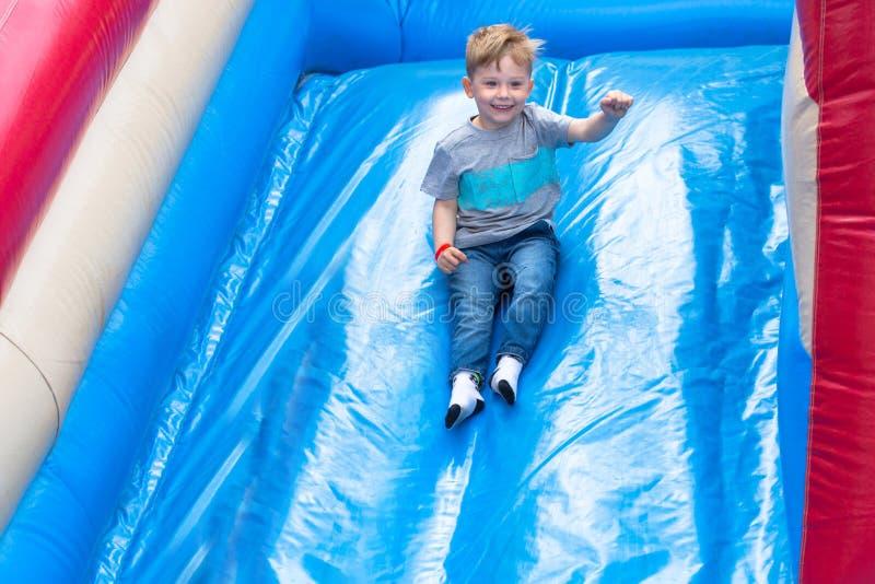 Peu de garçon ayant l'amusement sur la glissière dans le parc d'amusement image libre de droits