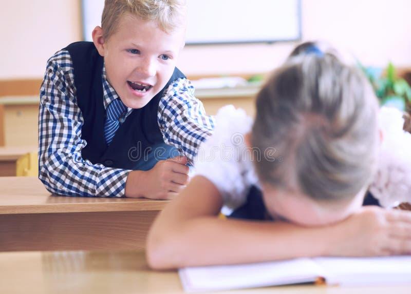 Peu de garçon d'étudiant d'école primaire essaye de déranger la fille pendant la leçon Le garçon essaye d'atteindre le ` s de fil photo libre de droits