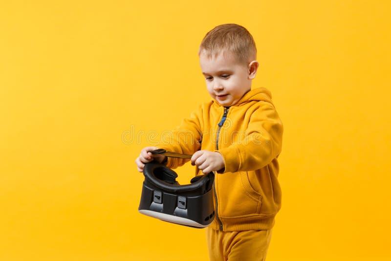 Peu de garçon d'enfant d'amusement 3-4 années utilisant les vêtements et le casque jaunes du vr sur des yeux d'isolement sur le f photo stock