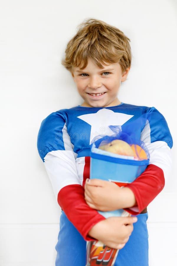 Peu de garçon d'enfant avec le sac d'école allemand traditionnel dans le costume de super héros photos stock