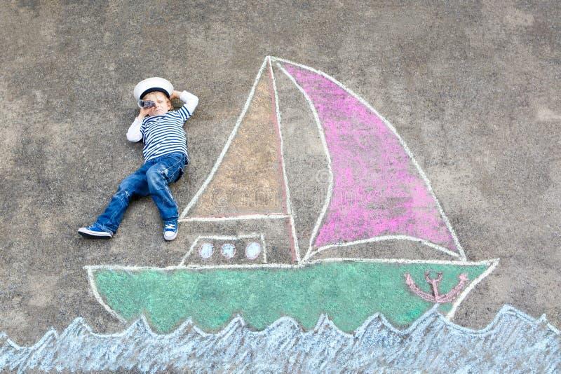 Peu de garçon d'enfant comme pirate sur la peinture de photo de bateau ou de sailingboat avec les craies colorées sur l'asphalte image stock