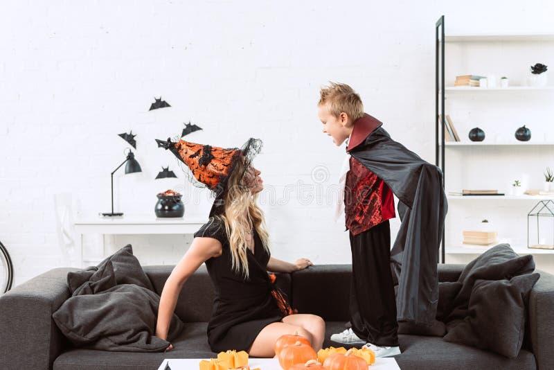 peu de garçon dans le costume de vampire criant à la mère dans le costume de Halloween de sorcière photos libres de droits