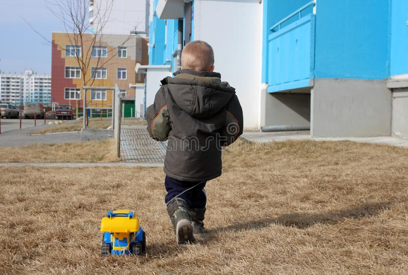 Peu de garçon a tourné le sien marchant de retour avec la machine de jouet sur la rue image stock