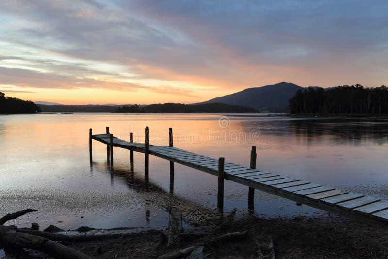 Peu de jetée de bois de construction sur le lac Wallaga au coucher du soleil photos libres de droits