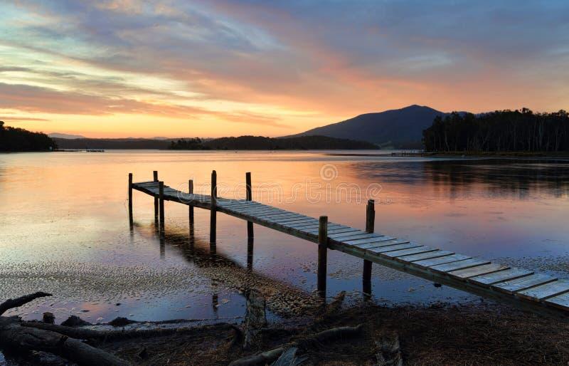 Peu de jetée de bois de construction sur le lac Wallaga au coucher du soleil photo libre de droits