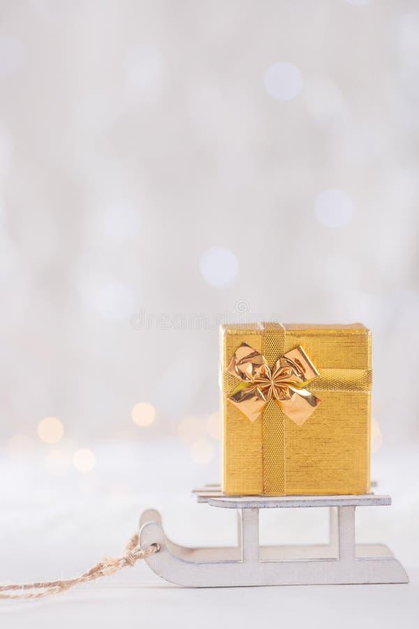 Peu de joli boîte-cadeau sur le traîneau blanc de jouet sur le backgrou léger de bokeh photo libre de droits