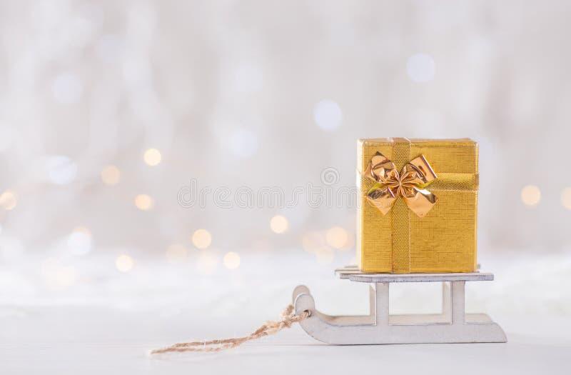 Peu de joli boîte-cadeau sur le traîneau blanc de jouet sur le backgrou léger de bokeh photo stock