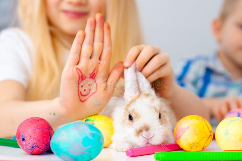 Peu de lapin de lapin avec les oeufs et les marqueurs colorés sur la table fille et garçon blonds sur le fond Prepearing pour Pâq image libre de droits