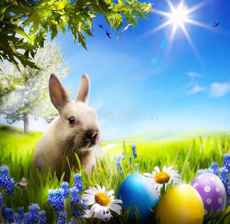 Art peu de lapin de Pâques et oeufs de pâques sur l'herbe verte photographie stock libre de droits