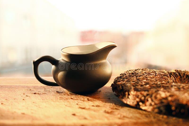 Peu de théière avec la brique de thé sur la table à la lumière du soleil images libres de droits