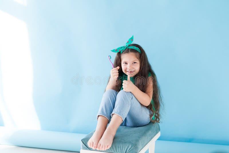 Peu dent de fille avec une bosselure de brosse à dents photo stock