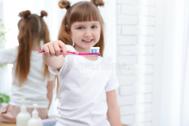 Peu dents de brossage de fille dans la salle de bains à la maison image libre de droits