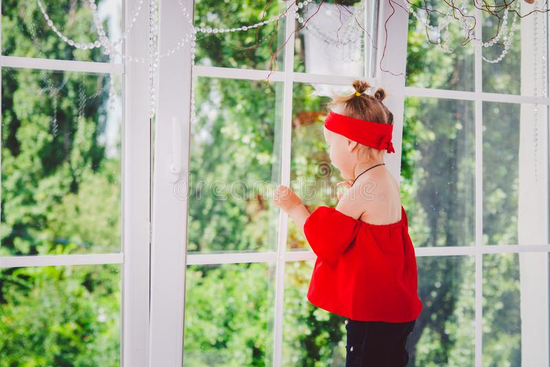 Peu deux années drôles de bébé dans les supports rouges élégants de vêtements et de jeans et d'espadrilles avec le dos sur le reb images stock