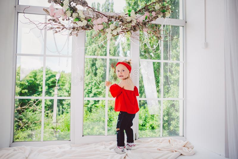 Peu deux années drôles de bébé dans les supports rouges élégants de vêtements et de jeans et d'espadrilles avec le dos sur le reb image stock