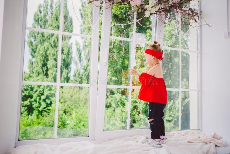 Peu deux années drôles de bébé dans les supports rouges élégants de vêtements et de jeans et d'espadrilles avec le dos sur le reb photo libre de droits