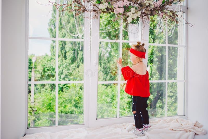 Peu deux années drôles de bébé dans les supports rouges élégants de vêtements et de jeans et d'espadrilles avec le dos sur le reb photos libres de droits