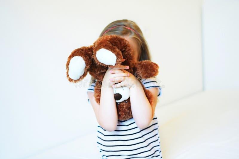 Peu a effrayé l'enfant se cachant derrière l'ours de nounours images stock