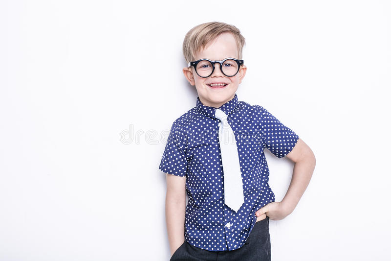 Peu enfant adorable en lien et verres école précours Mode Portrait de studio d'isolement au-dessus du fond blanc photographie stock libre de droits