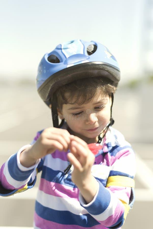 Peu enfant ajustant le casque de vélo dans le jour ensoleillé photo stock