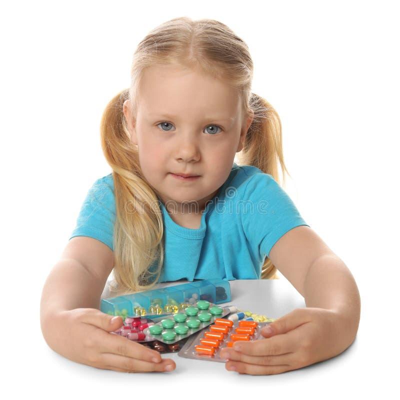 Peu enfant avec beaucoup de différentes pilules sur le blanc Danger d'intoxication de m?dicament image stock