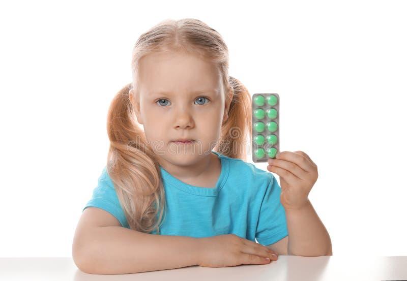 Peu enfant avec des pilules sur le blanc Danger d'intoxication de m?dicament photos stock