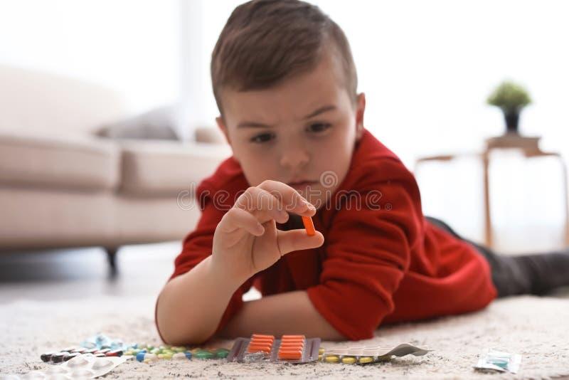Peu enfant avec différentes pilules sur le plancher Danger de ménage photo libre de droits